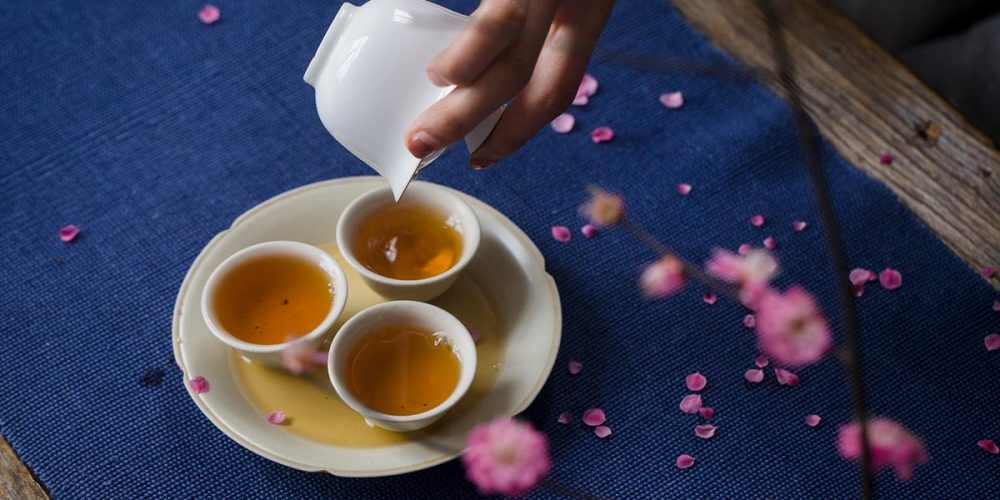 tea is poured from gaiwan to small teacups in traditional Chinese tea ceremony