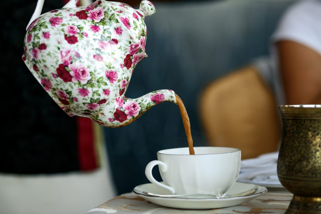Tea pouring from the teapot into a cup