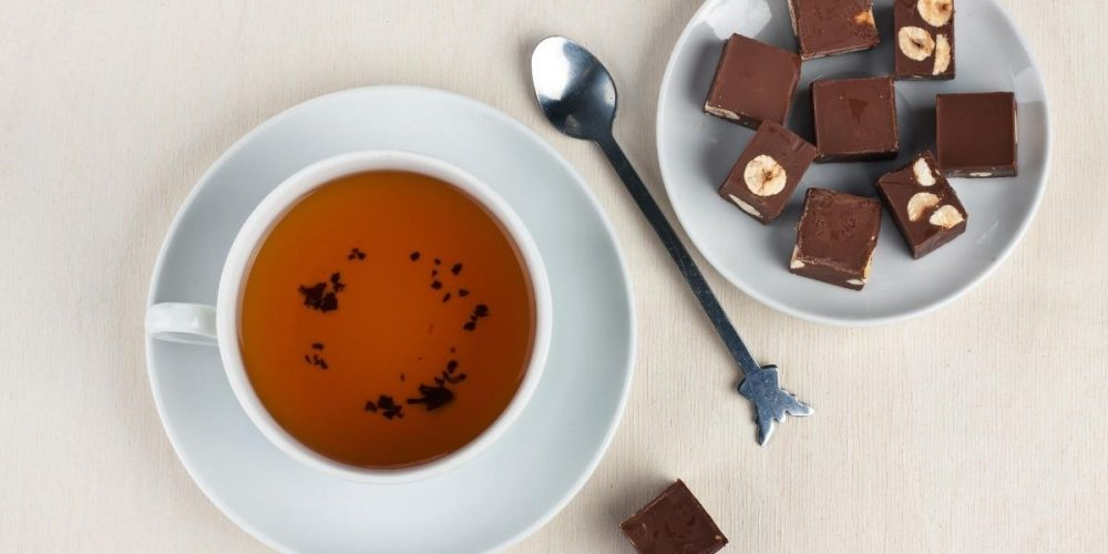 A cup of tea and a plate with chocolates