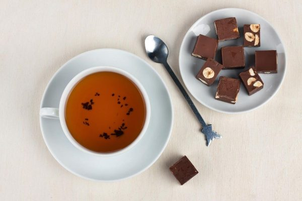 A cup of tea and a plate of chocolates on the table