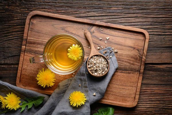 still life with a cup of tea, dandelion flowers, and pieces of dandelion root