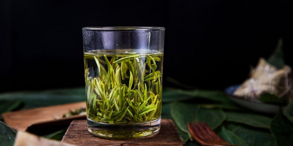 green tea leaves steeped in clear glas