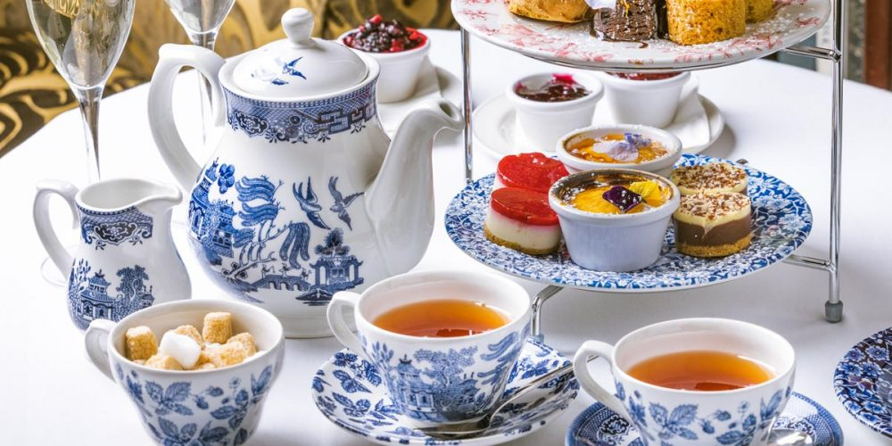 teacups, teapot, and plates with pastries in a traditional afternoon tea setting