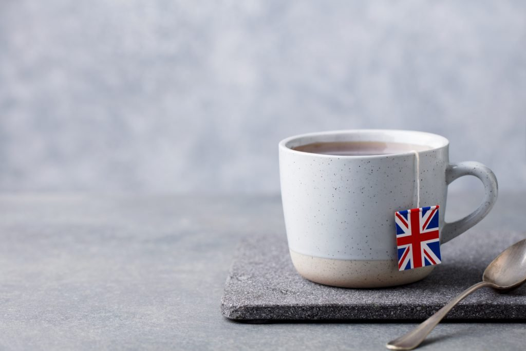 a cup of tea with a teabag and British flag symbol on it