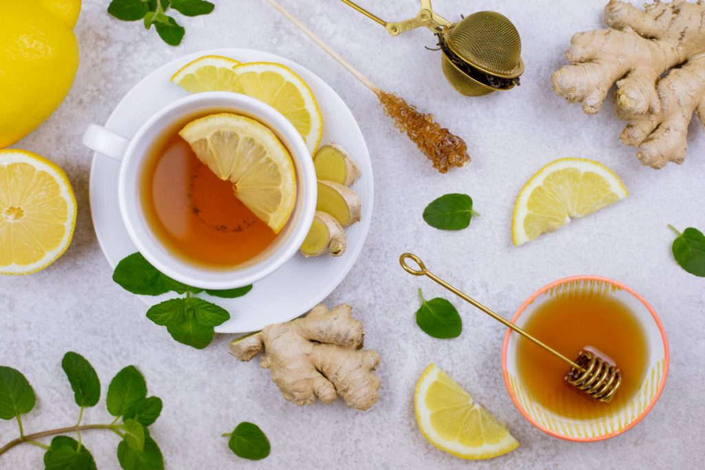 tabletop with a cup of tea, honey, and pieces of lemon and ginger