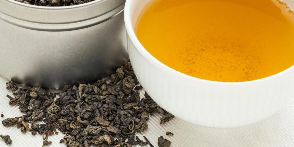 Gunpowder loose tea and tea cup on the table