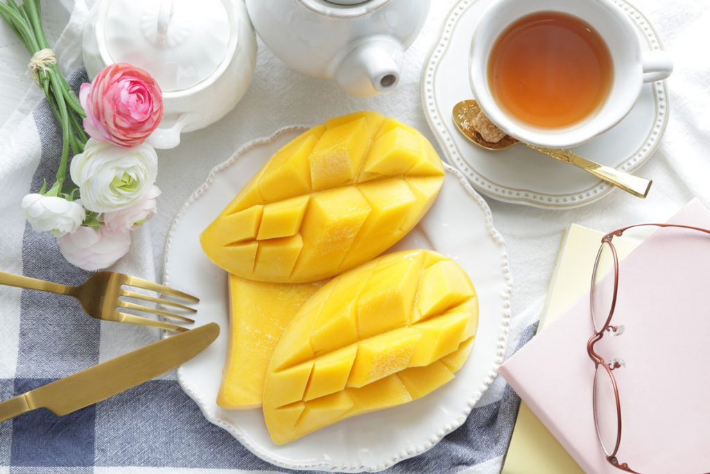 a cup of tea and a plate with mango slices