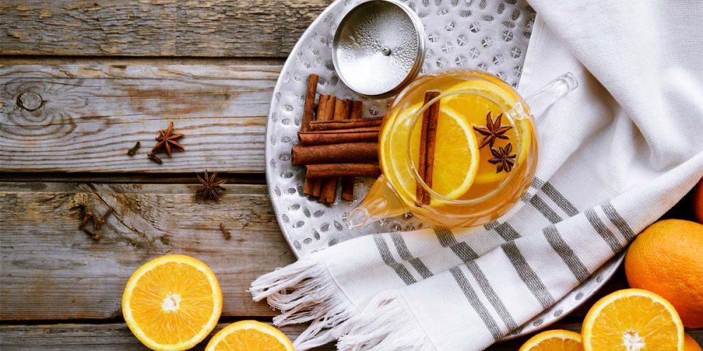teapot filled with tea, orange slices, cinnamon sticks