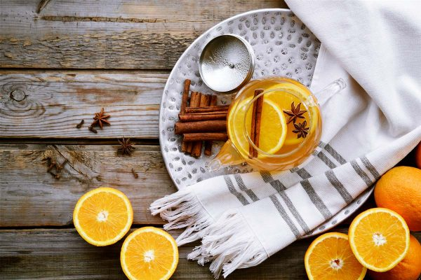 teapot filled with tea, orange slices, cinnamon sticks