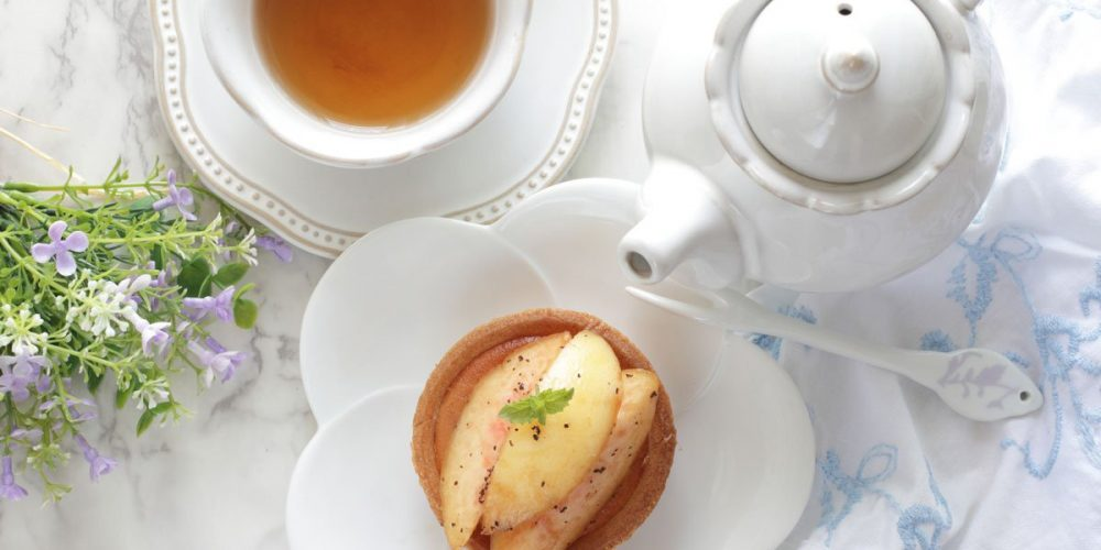 a cup of tea, a teapot, and a plate with peach slices