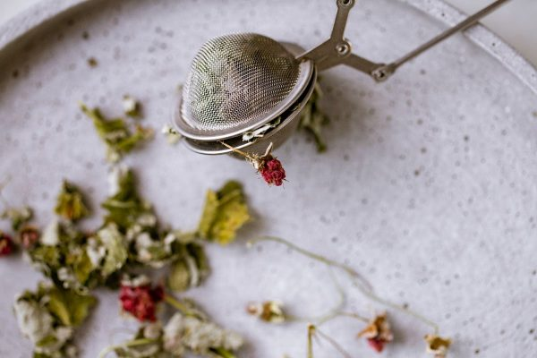 tea strainer with dried herbs and dried raspberries