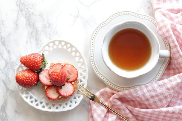 a cup of tea and a plate with strawberries