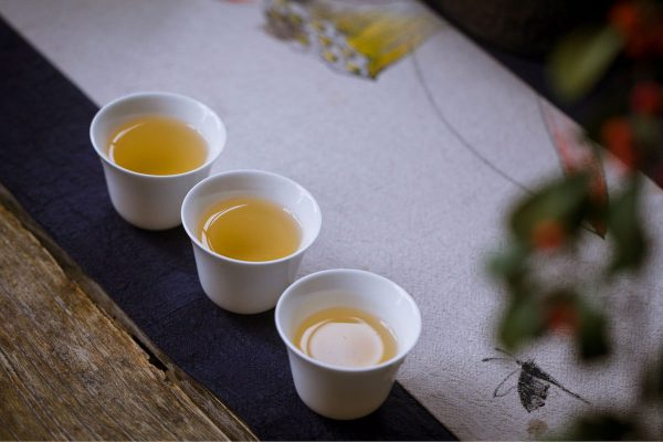 three teacups with tea in a traditional Chinese setup