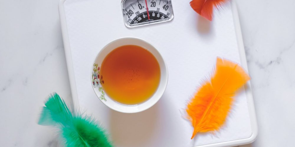 Cup of tea and feathers on a scale