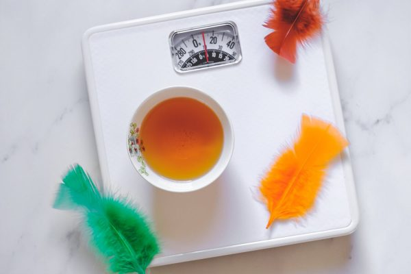 a cup of weight-loss tea on scale