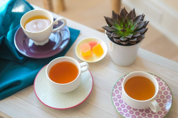 Three cups of tea on a table, sweets and flowers