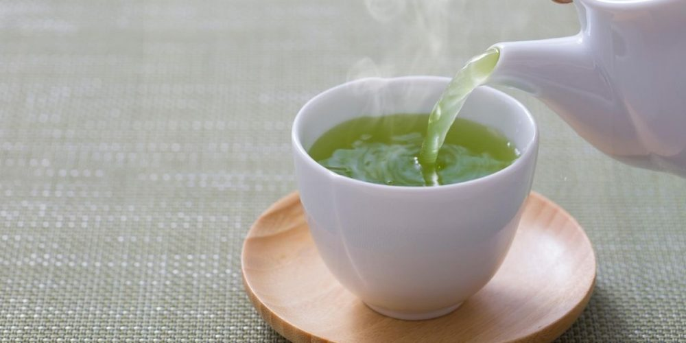 hot green tea pouring into teacup