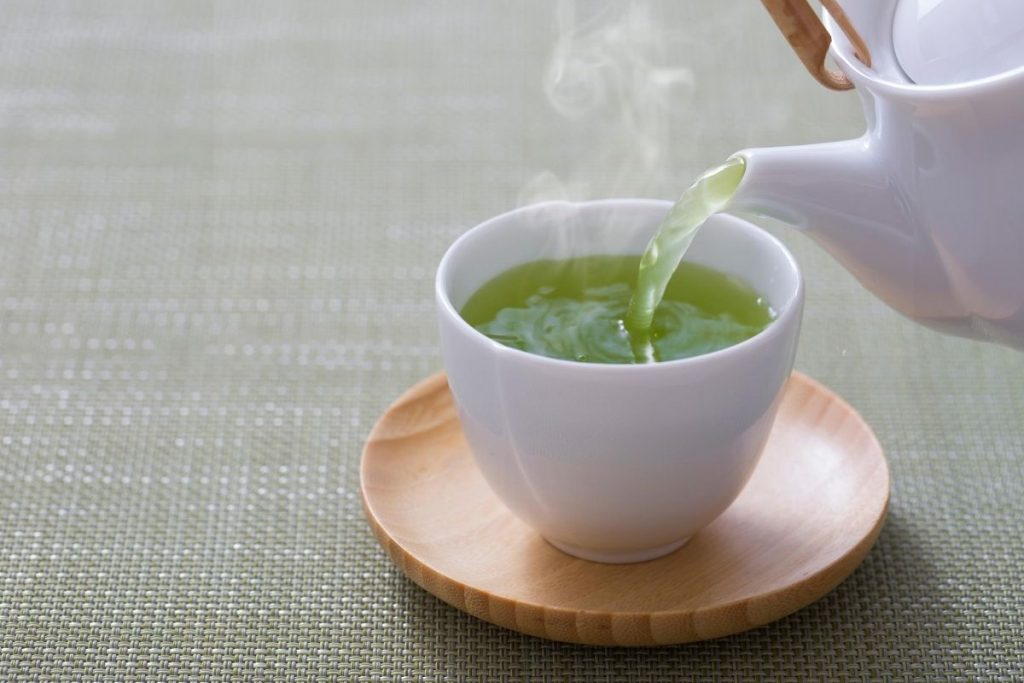 hot green tea pouring into teacup