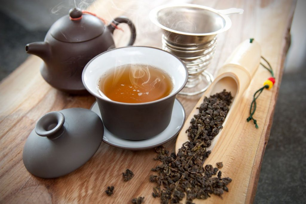 a cup of Oolong tea, teapot, tea leaves in a measuring spoon
