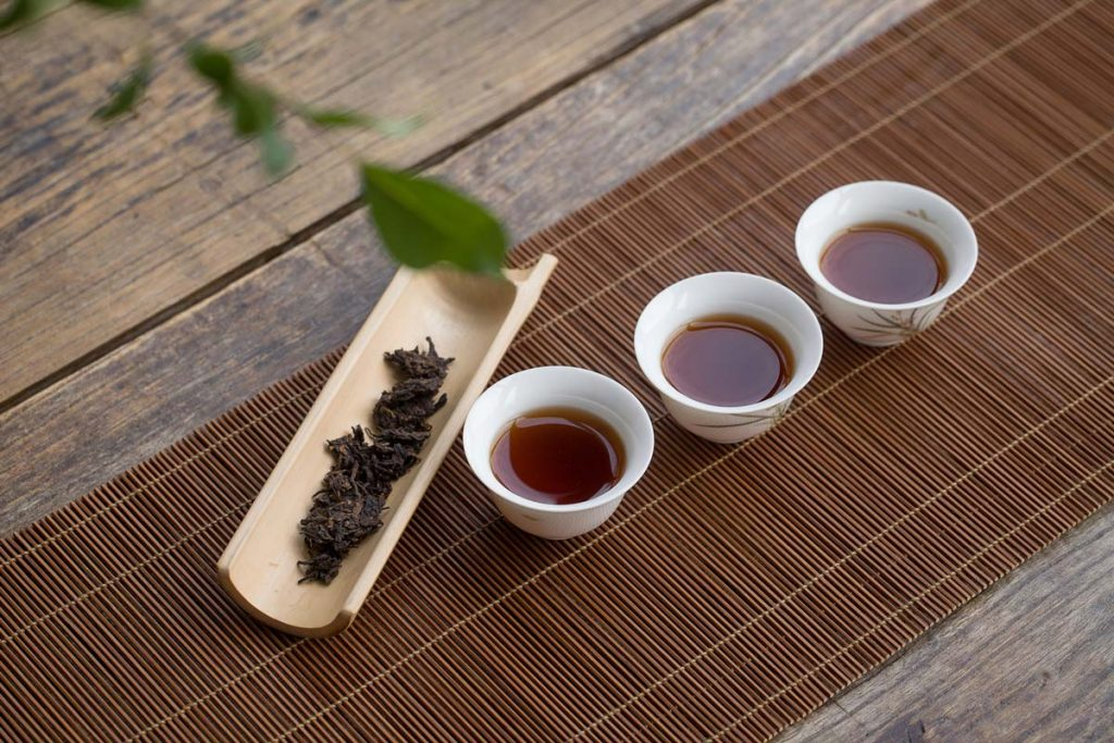 Three Teacups And Leaves Of Pu-Erh Tea