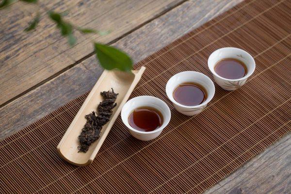 Three Teacups And Leaves Of Pu-Erh Tea