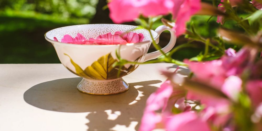 Cup of tea next to flowers