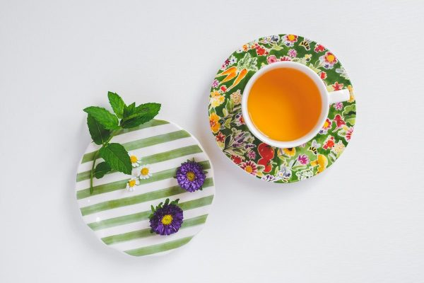 Cup of teas, herb leaves and flowers on a plate