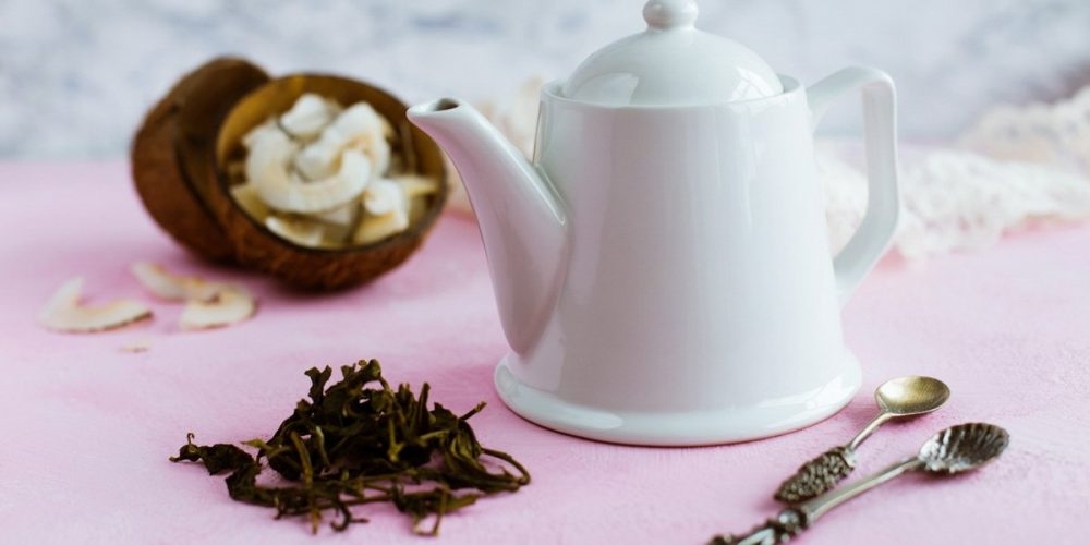 teapot, tea leaves, and coconut pieces in the background