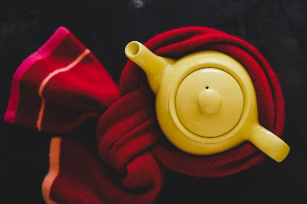 teapot with tea for colds wrapped in scarf