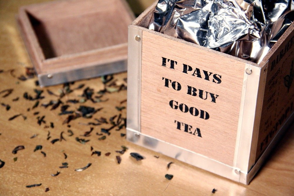 "wooden box filled with tea, wording on panel say ""it pays to buy good tea"""