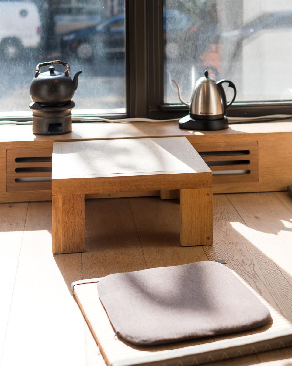 tea table by the window and seating floor mat next to it