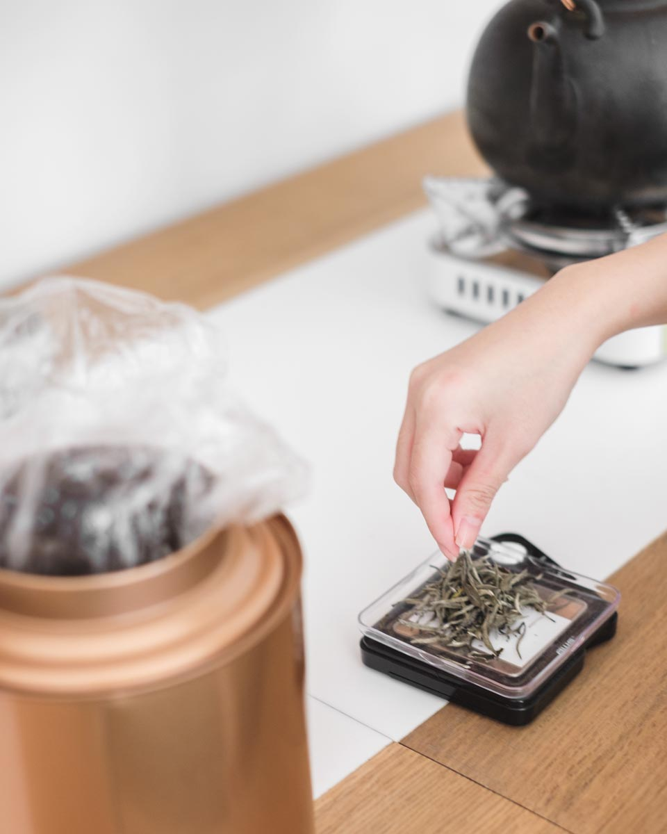 female hand putting tea leaves on scale