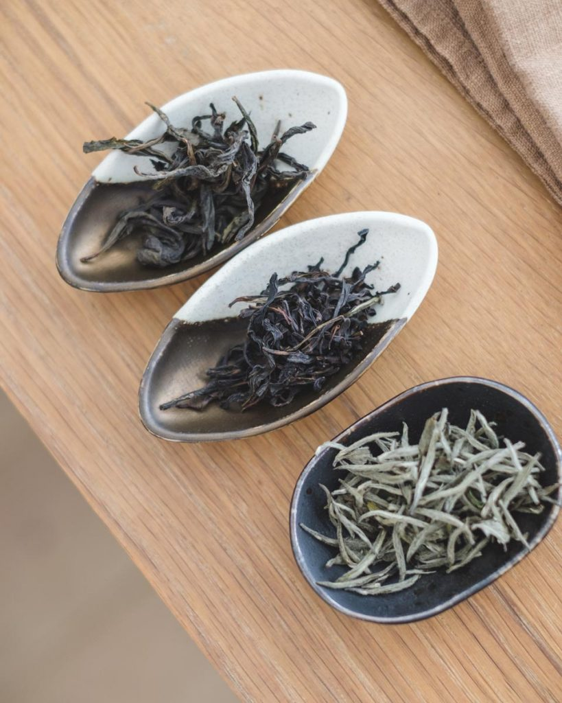 three small dishes with dry tea leaves