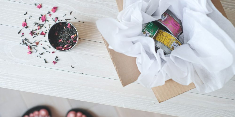 Tea Tins in a box, opened tin on a table