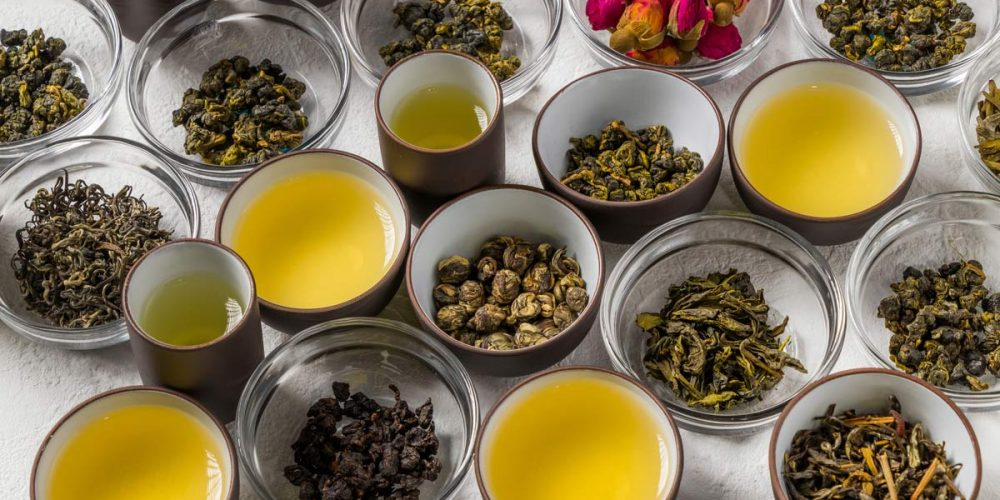 different kinds of tea in cups and glass bowls
